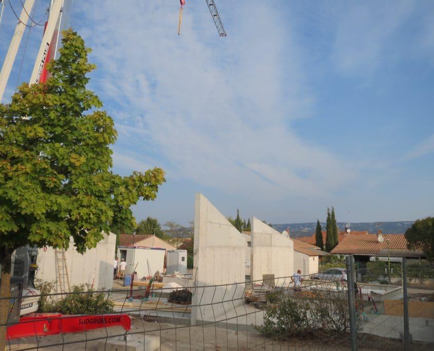 Vue depuis la route - phase maçonnerie. Les murs en béton banché améliorent le confort thermique et acoustique entre logements